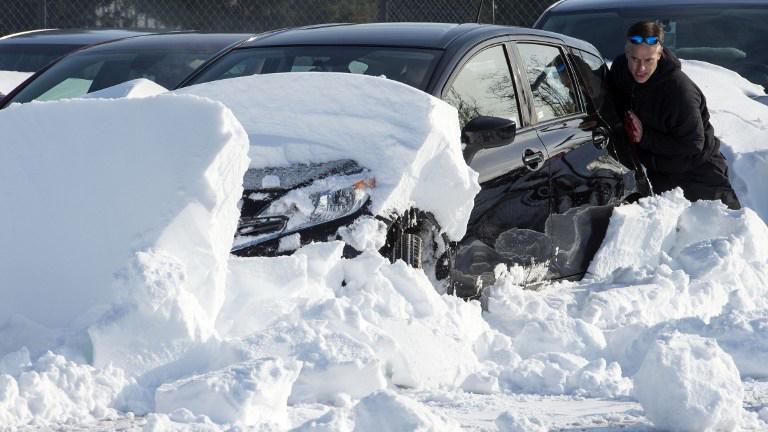Un conductor empujando su vehículo tras quedar cubierto por la nieve.