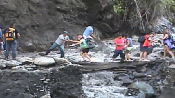 Sin medir el peligro, turistas cruzan vía obstruida por huaicos.