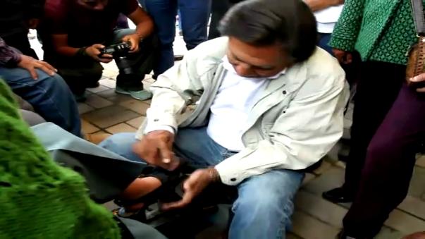Alejandro Toledo lustra zapatos a una pobladora en Junín