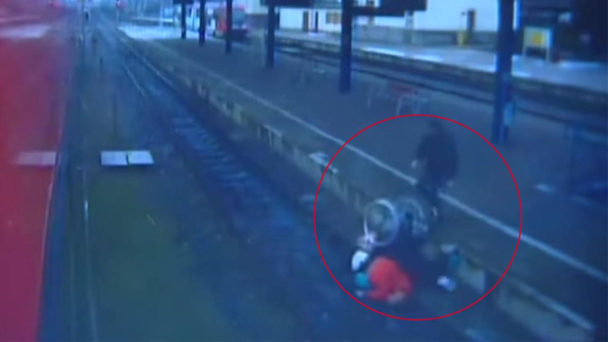 El hombre empuja a la mujer en silla de ruedas a las vías del tren.