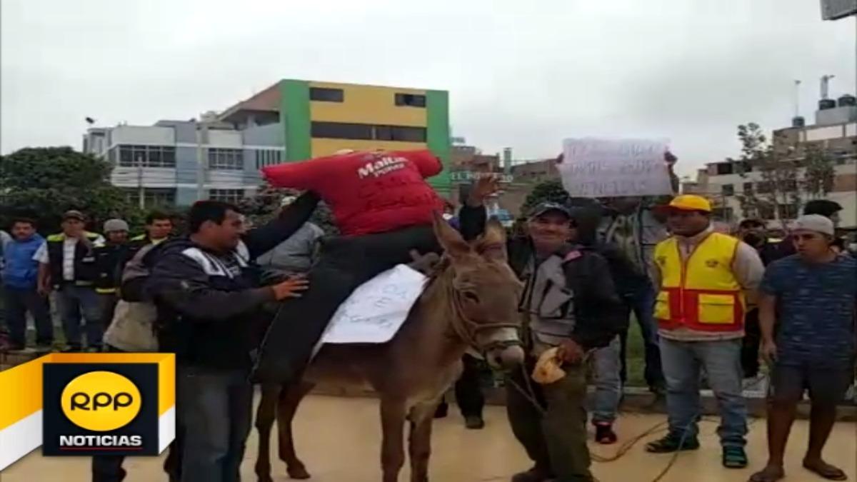 El asno que utilizaron en sus protestas  llevaba  un muñeco con el nombre del gerente distrital, Carlos Segura.