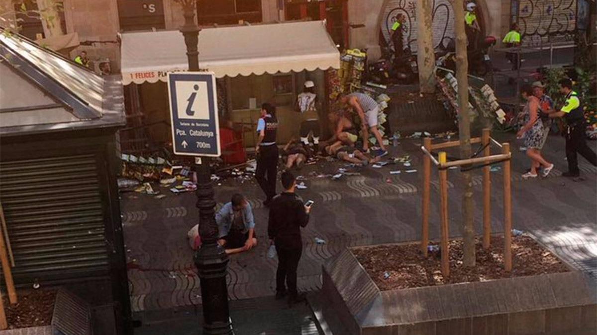 Atentado en Barcelona | La Rambla luego del ataque. En la foto se ve a algunas personas atendiendo a los heridos.
