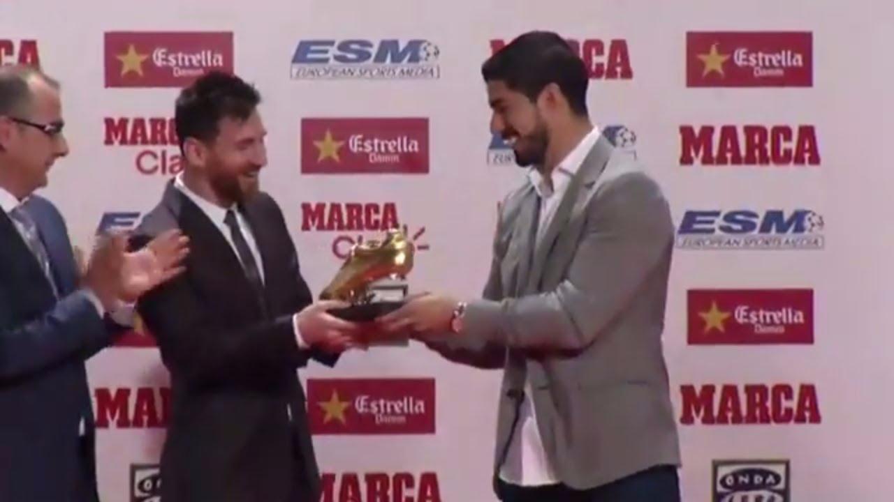 Lionel Messi recibe la Bota de Oro de manos de su compañero Luis Suárez.